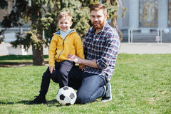 Young father and his son playing football in a park Royalty Free Stock Photography