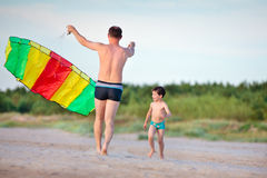 Young father and his son playing with kite. On the beach Royalty Free Stock Photo