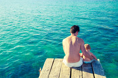 Young Father with His Son Relaxing by the Sea Stock Photo
