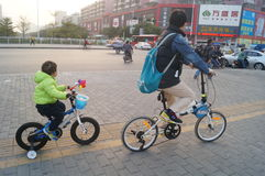 Young father and his son riding a bike together Royalty Free Stock Photos