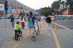 Young father and his son riding a bike together Stock Photography