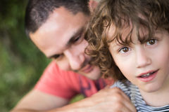 Young father with his son. Sunny summer nature. Young father with his cute little son. Sunny summer day in nature. Close up Stock Image