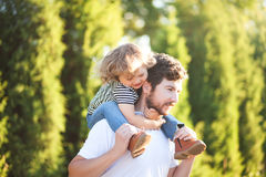 Young father and his toddler girl, riding on his shoulders Royalty Free Stock Image