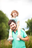 Young father and his toddler girl, riding on his shoulders Stock Images