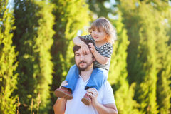 Young father and his toddler girl, riding on his shoulders Stock Photos