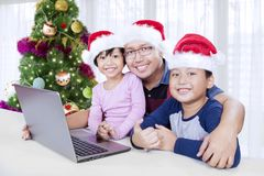 Father and children with laptop at Christmas time Stock Images
