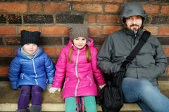Young father and his two little daughters sitting on a bench stock image