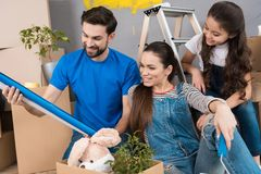 Young father and his wife and daughter sort things out from cardboard boxes in house they moved. Moving young family to new apartment stock photo
