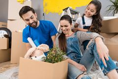 Young father and his wife and daughter sort things out from cardboard boxes in house they moved. Moving young family to new apartment royalty free stock photography