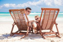 Young father and his wonderful daughter sitting on. Beach wooden chairs looking at camera. This image has attached release stock photos