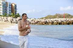 Young father holding baby on the beach near ocean with lighthous Royalty Free Stock Image