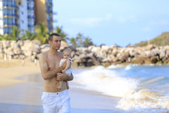Young father holding baby on the beach near ocean with lighthous Royalty Free Stock Photos