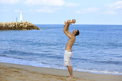Young father holding baby on the beach near ocean with lighthous Stock Images