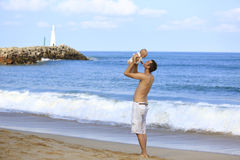 Young father holding baby on the beach near ocean with lighthous Royalty Free Stock Photo