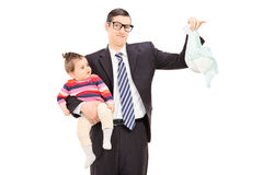 Young father holding a baby and a dirty diaper  Royalty Free Stock Photography