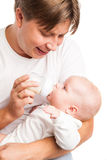 Young father holding and feeding her baby Royalty Free Stock Photography