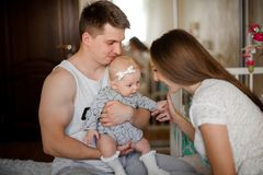 Father holding her little daughter on hands and mother on the be Royalty Free Stock Photos