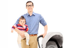Young father holding his baby daughter and baby stroller Royalty Free Stock Photos