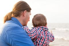 Young father holding his child on the beach Royalty Free Stock Image