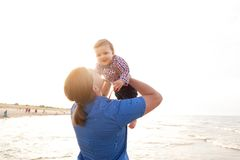 Young father holding his child on the beach having fun together Stock Image