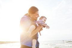 Young father holding his child on the beach having fun together Royalty Free Stock Photo