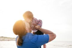 Young father holding his child on the beach and kissing Stock Photography