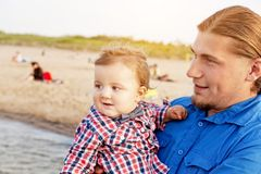 Young father holding his child on the beach portrait Stock Photography