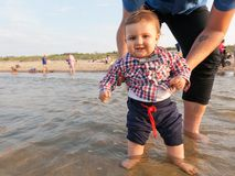 Young father holding his child over sea water stock photos