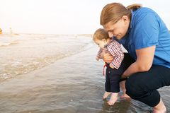 Young father holding his child over sea Royalty Free Stock Images