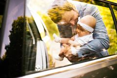 Young father with his little baby girl going into the car. Stock Photo