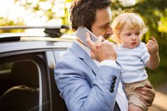 Young father with his little boy and smartphone at the car. Royalty Free Stock Photography