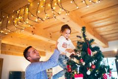 Young father with daugter decorating Christmas tree together. Young father holding his little daughter in his arms at home decorating Christmas tree together Stock Photos