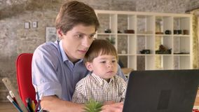 Young father holding his little son and working on laptop, busy, sitting in modern office.  stock footage