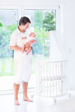 Young Father Holding His Newborn Baby Next To Crib Royalty Free Stock Images