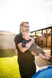 Young father holding his son above a pool Stock Photography