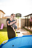 Young father holding his son above a pool. The baby is smiling at the camera Royalty Free Stock Photo
