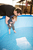 Young father holding his son above a pool. The baby is testing the water Stock Images