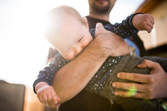 Young father holding his son in the sun Royalty Free Stock Photo