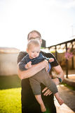 Young father holding his son at sunset Stock Images