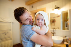 Young father holding his son wrapped in towel after bathing him Royalty Free Stock Image