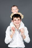 Young father holding little son on his shoulders. On grey Stock Photos