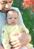 Young father holding serious baby stock photos