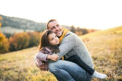 A young father having fun with a small daughter in autumn nature. stock photo