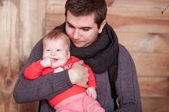 Young father holding son against wooden background. Vertical shot Stock Photo