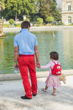 Young father holds daughter's hand in Luxembourg Garden, Paris. Young father in red slacks and blue polo shirt holds little girl's hand as they look over the Royalty Free Stock Image