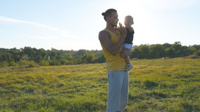 Young father holds on hands his son in the meadow at nature at sunny summer day. Dad and little boy hugging outdoor and. Giving five to each other. Beautiful Royalty Free Stock Photography