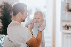Young father holds in his arms his tiny sun on the sofa in the light room stock photography