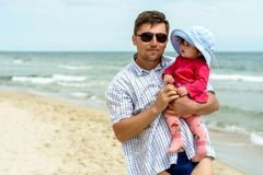 A young father holds his daughter`s hands on the beach royalty free stock photos