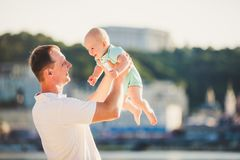 A young father holds one year of his son in his arms with a smile and loves hugs and throws him on the river bank on the beach.  royalty free stock images
