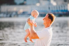 A young father holds one year of his son in his arms with a smile and loves hugs and throws him on the river bank on the beach.  stock photo